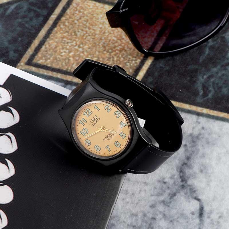 ساعة يد عملية كاجوال بسوار اسود و قرص بمؤشرات ارقام مضيئة ليلاً بخلفية لون نحاسي متجر 15 وأقل
