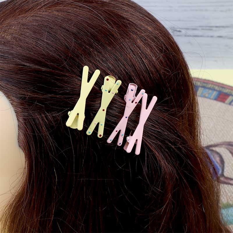 قطعتان من مشابك الشعر بتصميم علامة ضرب لون اصفر و وردي متجر 15 وأقل